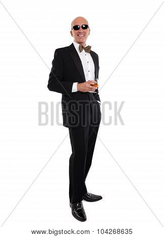 Man in a tuxedo standing holding a drink