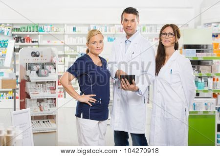Portrait of confident pharmacists with digital tablet standing in pharmacy