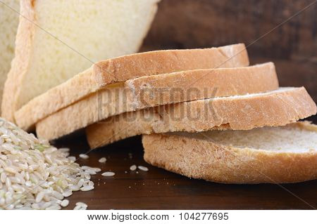 Gluten free rice sliced sour dough bread with raw brown rice on dark wood table background. poster