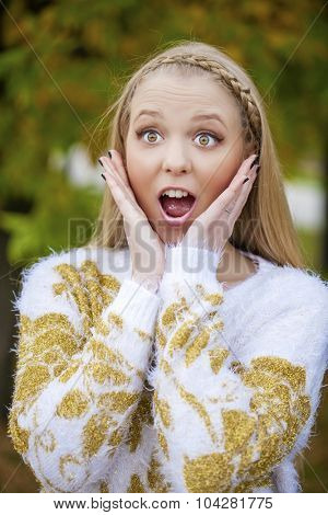 Close up portrait of a young caucusian woman with blond hair scared, afraid and anxious. Screaming, with eyes wide open. Human emotions. Parody on a Munch Scream, outdoors in autumn park