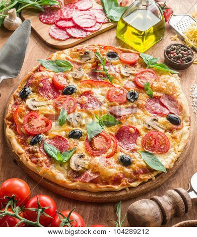 Pizza with mushrooms, salami and tomatoes. Top view. poster