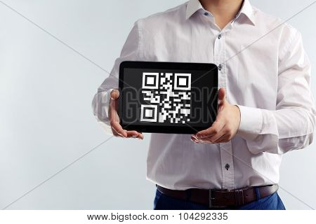 Businessman holding tablet PC with QR code on screen