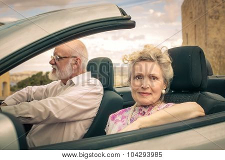 Elderly couple travelling by car