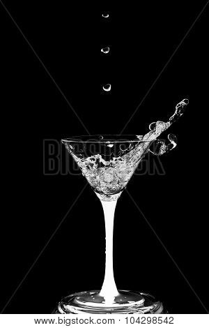 Cocktail Glass With Splashes Isolated On A Black Background.