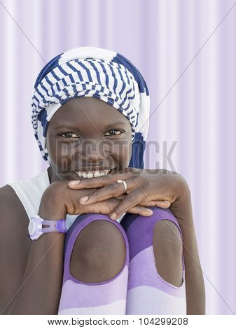 Smiling girl wearing a striped headscarf, ten years old
