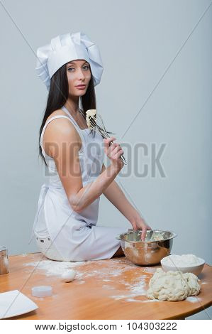 sexy  woman in chef uniform knead the dough on white background poster