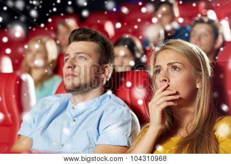 cinema, entertainment and people concept - terrified friends or couple watching horror, drama or thriller movie in theater with snowflakes