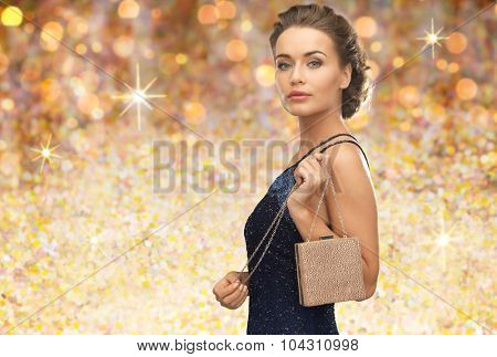 people, holidays, luxury and glamour concept - woman in evening dress with small handbag over golden lights background