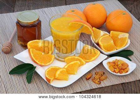 Health food for cold cure relief with freshly squeezed orange fruit juice, vitamin c tablets and honey on bamboo over oak background.