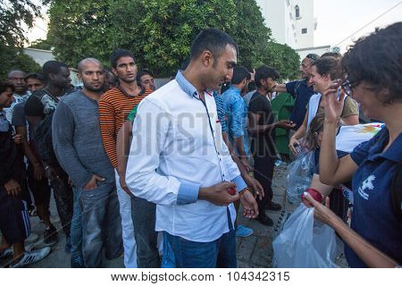 KOS, GREECE - SEP 27, 2015: War refugees receive humanitarian assistance. More than half are migrants from Syria, but there are refugees from other countries-Afghanistan, Pakistan, Iraq, Iran.