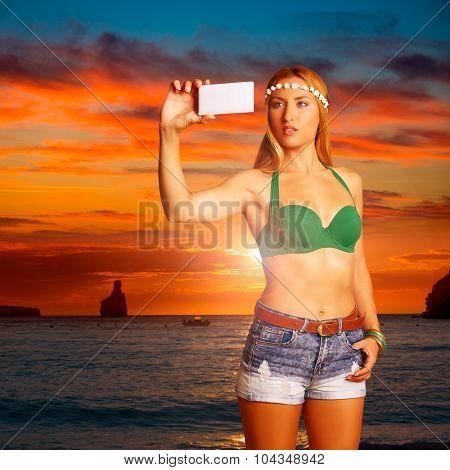 Blond tourist girl taking selfie photo in Benirras beach at Ibiza sunset photomount