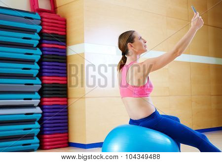 Pilates woman shoots selfie self portrait with mobile at gym relaxed with fitball