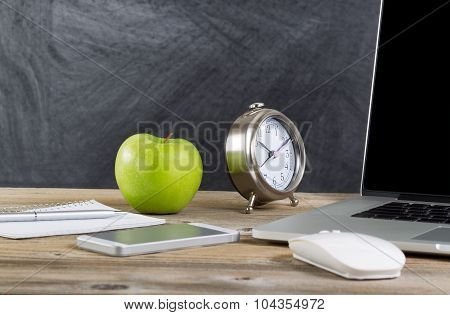 Old Wooden Desktop With Technology And Green Apple