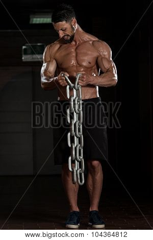 Healthy Young Bodybuilder Exercising Biceps With Chains poster