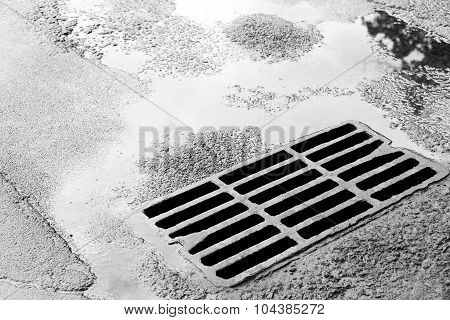 Sewer Grate On Wet Road With Puddles