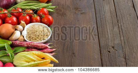 Unpolished raw rice and vegetables on a wooden background poster