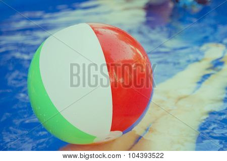 Colorful beach balls floating in pool