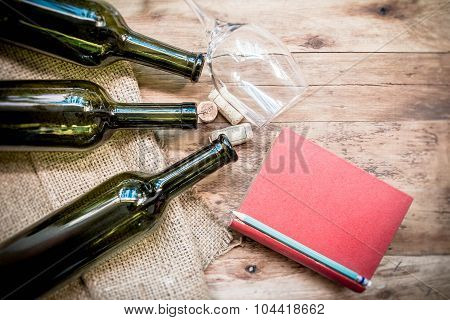 Red Wine Bottle, Glass And Grape Shaped Corks And Red Book On Wooden Table