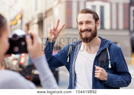 Cheerful young tourists are making photos in town