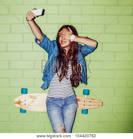 Beautiful Long-haired Girl With A Cellphone Near A Green Brick Wall