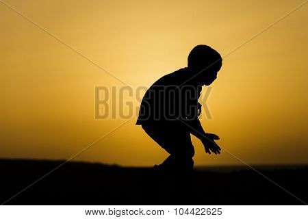 Sihouette Of A Boy In Front Of The Setting Sun