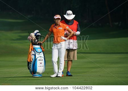KUALA LUMPUR, MALAYSIA - OCTOBER 09, 2015: South Korea's Il Hee Lee discusses with her caddy on the 6th hole fairway of the KL Golf & Country Club at the 2015 Sime Darby LPGA Malaysia golf tournament.