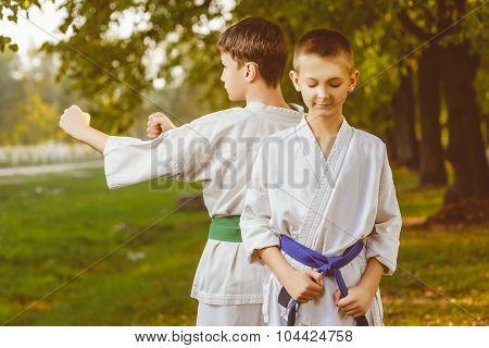 boys in white kimono during training karate exercises at summer outdoors
