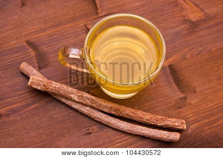 Herbal tea licorice inside cup on wood from above