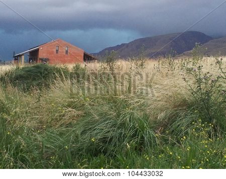 House in the field under the storm