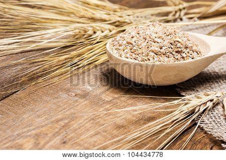 Wheat Bran In Wooden Spoon With Wheat Ears