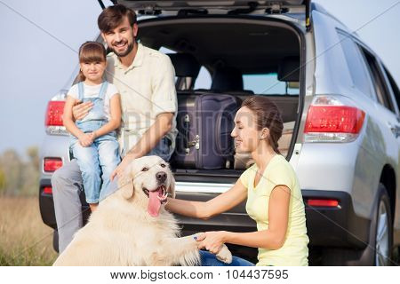 Cute parents are child with pet near transport