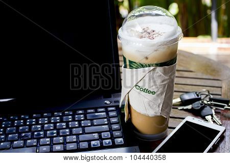 Iced Cappuchino On A Table With Smart Phone And Notebook
