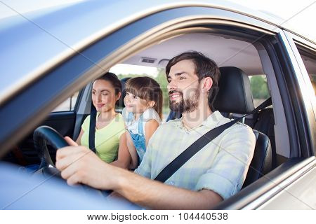 Pretty parents and child are traveling by vehicle