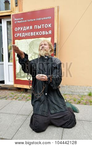 Wax Statue Of Prisoner In Chains At The Entrance Of Museum Of Medieval Torture Instruments In Saint