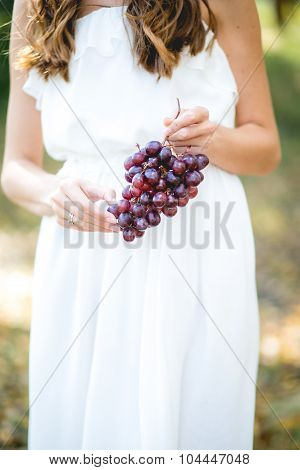 Beautiful Young Woman With Grape Bunches Against Summer Green Park.