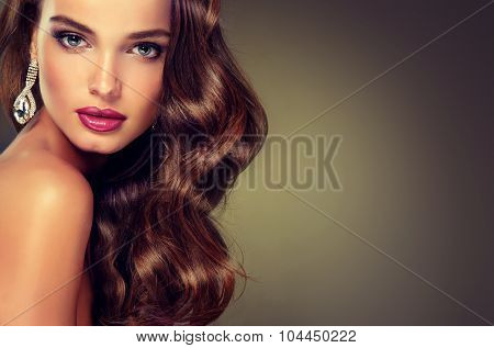 Beautiful model brunette with long curled hair. Fashion  jewelry earrings   and trendy makeup