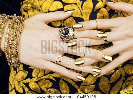 woman hands with golden manicure lot of jewelry on fancy dress