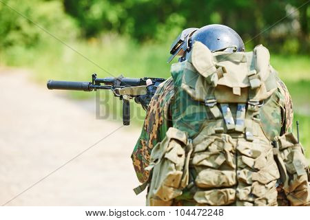 military. two soldier with assault rifle in uniform patrolling territory outdoors