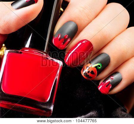 Halloween Nail art design. Nail Polish. Beauty hands. Trendy Stylish Colorful Nails and Nailpolish. Black matte nailpolish with blood drips and pumpkin