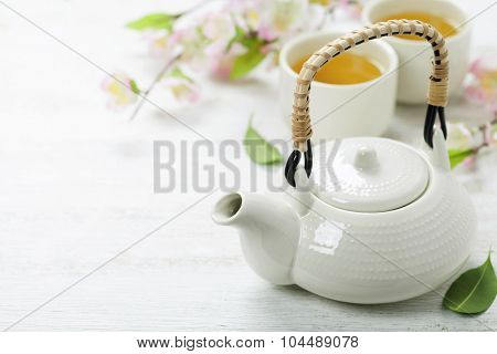 Chinese Tea Set  and sakura branch on bamboo mat