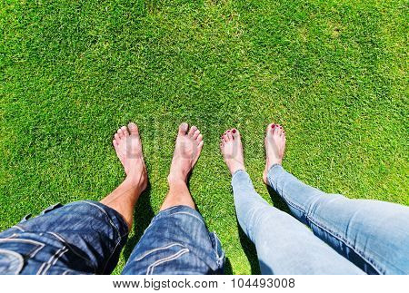 Two pairs of bare feet standing on the grass