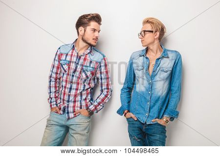relaxed casual young men looking at eachother while standing with hands in pockets in studio
