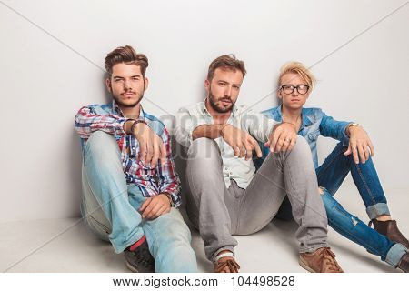 three casual men having a break and rest sitting down on the floor of the studio