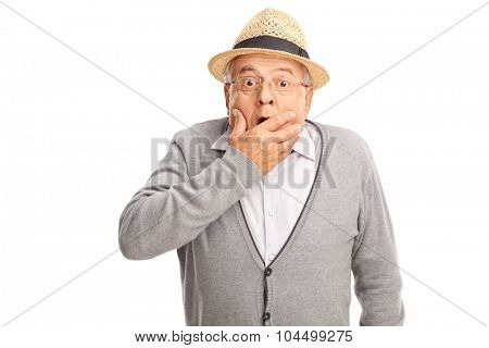 Shocked senior gentleman holding his hand against his mouth and looking at the camera isolated on white background
