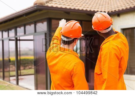 rear view of contractors pointing at house under construction