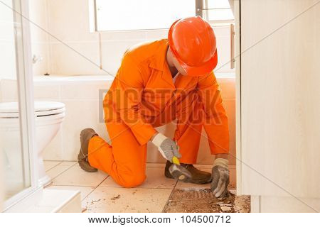 constructon worker removing old floor tiles using a hammer and chisel