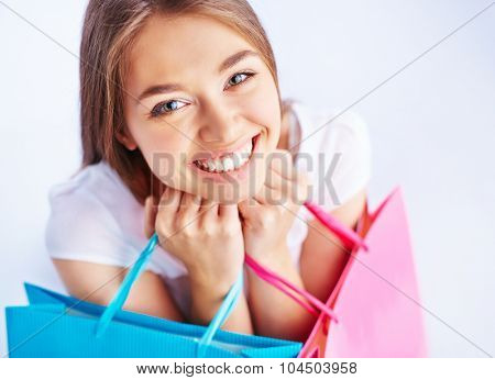 Female shopper with paperbags looking at camera with toothy smile