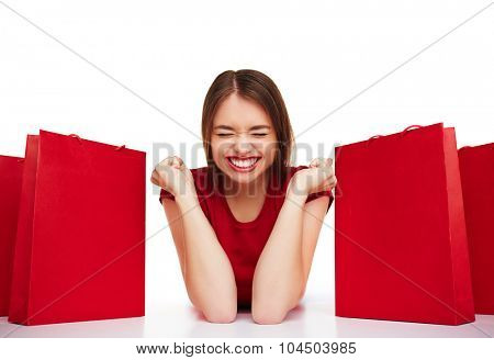 Joyful girl with expression of triumph lying between red paperbags