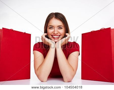 Smiling girl looking at camera between two red paperbags
