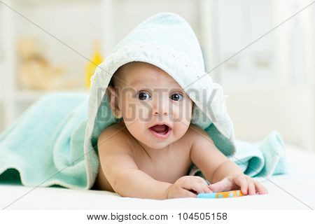Adorable baby boy under a hooded towel after bathing